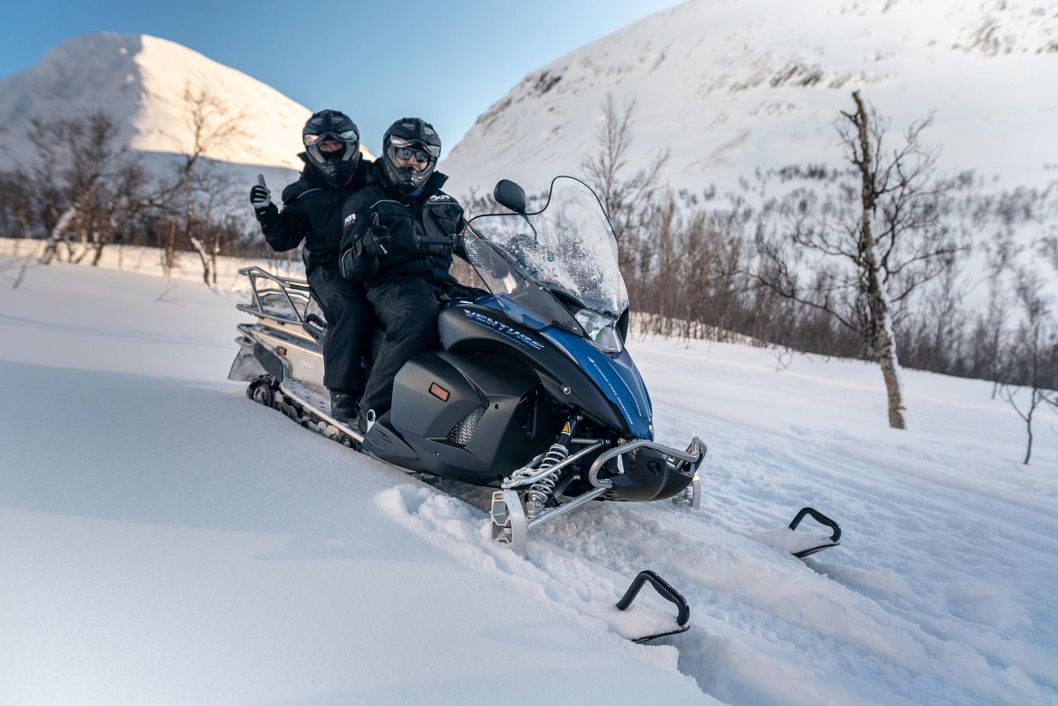 to personer på en snøscooter
